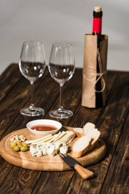 Bottle of wine, wine glasses, cheese, olives, sauce and bread on wooden surface stock vector