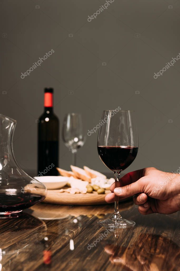 Cropped view of man holding wine glass at table in restaurant stock vector