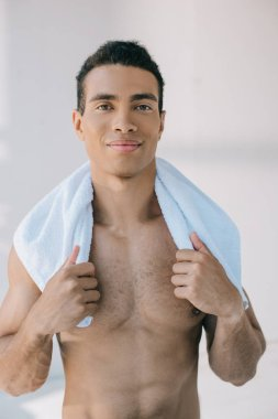 Muscular mixed race man holding blue towel on shoulders and looking at camera stock vector