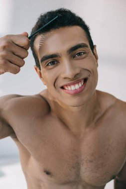 Handsome mixed race man combing hair with hairbrush and smiling while looking at camera stock vector