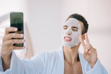 young man in bathrobe with cosmetic mask on face taking selfie on smartphone and showing victory sign