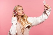 Photo beautiful blonde woman with headphones taking selfie on smartphone with duck face isolated on pink