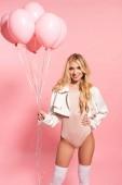 schöne blonde sexy Mädchen hält rosa Ballons auf rosa