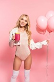 beautiful blonde happy girl holding pink balloons and beverage on pink