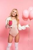 gyönyörű szőke boldog lány gazdaság rózsaszín léggömbök és italt a rózsaszín