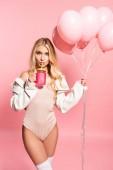 schöne blonde Frau trinken aus Stroh und halten Luftballons auf rosa