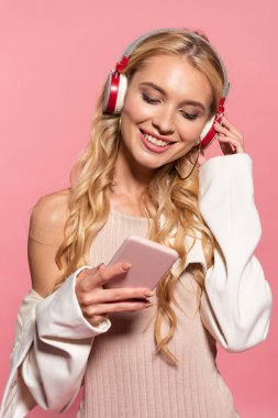 beautiful blonde happy woman with headphones using smartphone isolated on pink