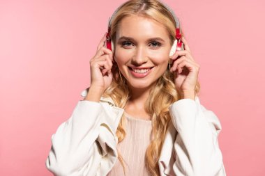 beautiful blonde happy woman listening music in headphones isolated on pink