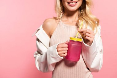 cropped view of beautiful blonde happy girl holding beverage with straw on pink