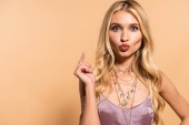 Photo elegant blonde woman in violet satin dress and necklace with duck face isolated on beige