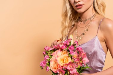 cropped view of elegant woman in violet satin dress holding bouquet of flowers isolated on beige with copy space