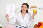 usměvavý DietOn v bílém kabátě, který drží papír s obrazem dokonalého těla a jablek na pracovišti s ovocem a zeleninou na stole