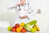 részleges kilátás dietetikus fehér kabát a sztetoszkóppal közelében friss gyümölcsök és zöldségek