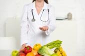 ostříhané zobrazení dietárního pláště a stetoskop s napřaženou rukou v blízkosti čerstvého ovoce a zeleniny
