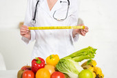 Fotografie cropped view of dietitian in white coat holding measure tape near fresh fruits and vegetables