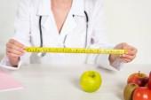 nyírt a dietetikus fehér kabát mérésére szalag és friss ételeket az asztalon