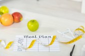 meal plan, measure tape, caliper, pen and fresh fruits on wooden surface