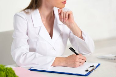 Partial view of dietitian in white coat writing in clipboard at workplace stock vector