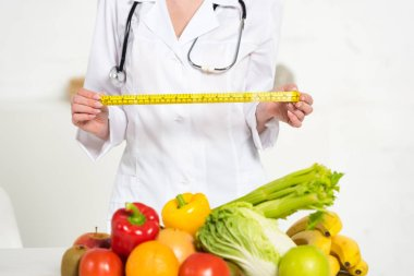 cropped view of dietitian in white coat holding measure tape near fresh fruits and vegetables