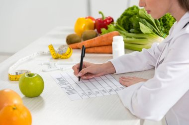 cropped view of dietitian writing in meal plan at workplace