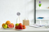 frisches Obst, Gemüse, Glas Wasser, Pillen, Lehrbuch und Schablone mit Inschrift Allergie auf dem Tisch