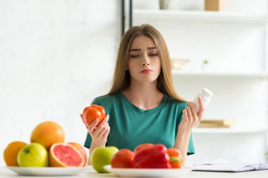 sad woman sitting at table with fruits and vegetables and holding pills and tomato