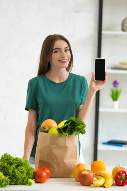Smiling girl standing near paper bag with food and holding smartphone with blank screen at home stock vector