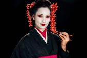usmívající se krásná gejša v černém kimonu s červenými květy ve vlasech s hůlky, izolované na černém