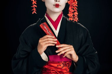 partial view of geisha in black kimono with red flowers in hair holding traditional hand fan isolated on black