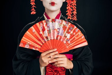 cropped view of beautiful geisha in black kimono with red flowers in hair holding traditional hand fan isolated on black