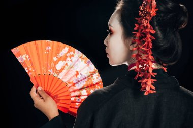 Back view of beautiful geisha in black kimono with red flowers in hair holding traditional hand fan isolated on black stock vector