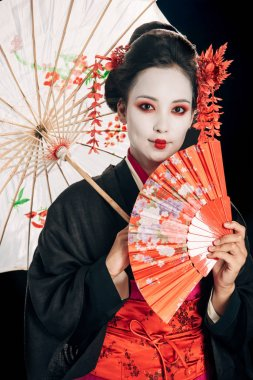 Smiling beautiful geisha in black kimono with red flowers in hair holding traditional asian umbrella and hand fan isolated on black stock vector