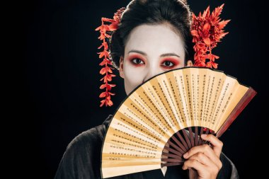 geisha in black kimono with red flowers in hair holding traditional asian hand fan near face isolated on black
