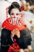 selektivní zaměření krásné gejša v černém kimonu s květinami ve vlasech s rukou ventilátorem před obličejem a sakury v kouřových větvích