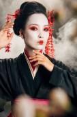 selektivní zaměření gejša v černém kimonu s červenými květy v dotyku vlasů blízko sakury větví na černém pozadí s kouřem