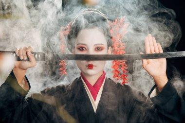 selective focus of geisha in kimono holding katana in smoke and sakura branches