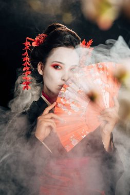 selective focus of beautiful geisha in black kimono with flowers in hair holding hand fan and sakura branches in smoke