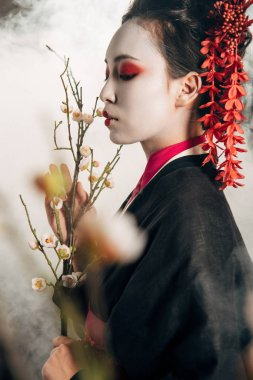 selective focus of beautiful geisha in black kimono with red flowers in hair and sakura branches in smoke