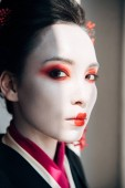 portrait of beautiful geisha with red and white makeup looking at camera in sunlight