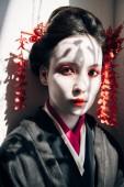 portrét nádherné gejša s červeným a bílým líčením, který se dívá na fotoaparát ve slunečním světle se stíny