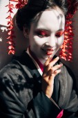 portrét usmívající se krásné gejša s červeným a bílým líčením na slunci se stíny