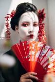 selektivní zaměření větví stromů a krásné gejša s červeným a bílým make-upem, přidržením ručního ventilátoru na slunci