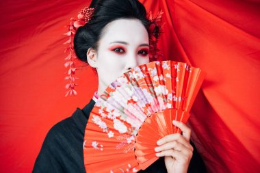 Beautiful geisha in black kimono with hand fan and red cloth on background stock vector