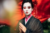 selektivní zaměření větví stromů a krásné gejša s gestem s pozdravem a červeným hadříkem na pozadí slunečního světla