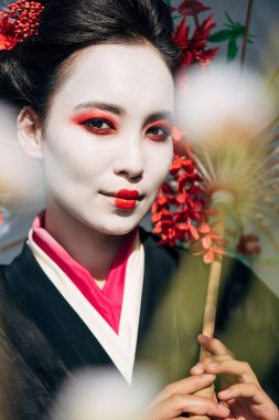 selective focus of tree branches and beautiful smiling geisha with umbrella in sunlight
