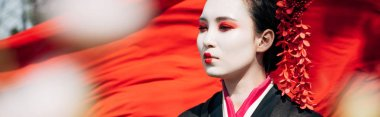 selective focus of tree branches and beautiful geisha with red cloth on background in sunlight, panoramic shot