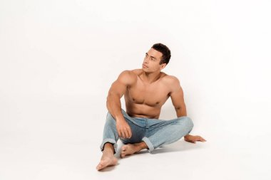 Pensive shirtless man sitting in blue jeans on white stock vector