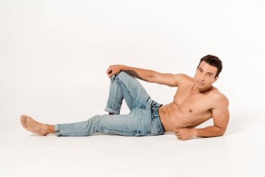 handsome shirtless man in blue jeans on white
