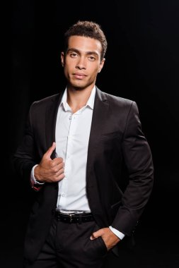 handsome mixed race man touching suit while standing with hand in pocket isolated on black
