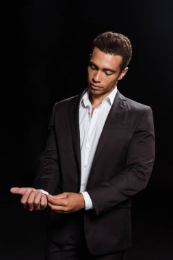 mixed race man standing and touching suit isolated on black